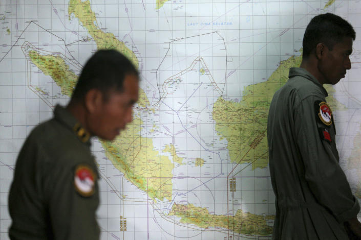 Indonesian Air Force officers stand against a map that shows a part of the South China Sea during a briefing following a search operation for the missing Malaysia Airlines Boeing 777, at Suwondo air base in Medan, North Sumatra, Indonesia, Thursday, March 13, 2014. The hunt for the missing jetliner has been punctuated by false leads since it disappeared with 239 people aboard about an hour after leaving Kuala Lumpur for Beijing early Saturday. (AP Photo/Binsar Bakkara)