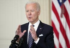 Biden speaks at a podium with the American flag behind him.