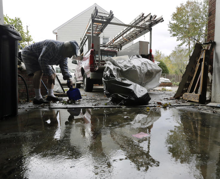Charlie DiBuono cleans mud and debris from his flooded garage in the wake of superstorm Sandy on Thursday, Nov. 1, 2012, in Little Ferry, N.J. Surprise coastal surge floods caused by the storm battered Little Ferry, Moonachie and some other towns along the Hackensack River in Bergen County _ all areas unaccustomed to flooding. (AP Photo/Mike Groll)