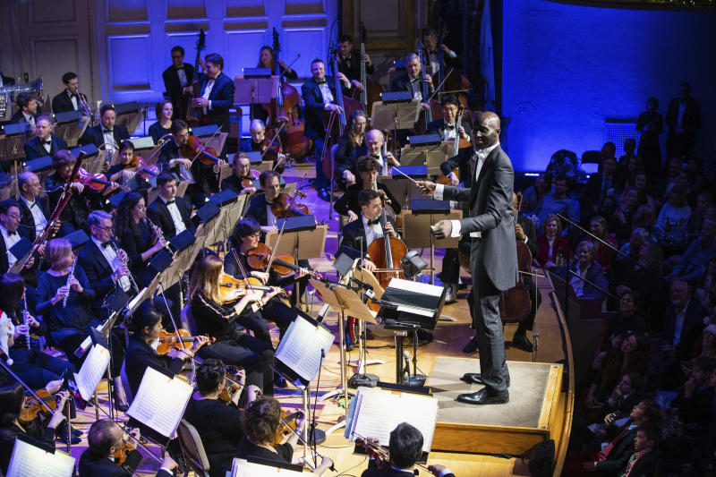 """In this Monday, Dec. 23, 2019, photo provided by Boston Pops, Boston Celtics player Tacko Fall makes his debut as a guest conductor during the renowned Boston Pops orchestra's holiday concert in Boston. The 7-foot-6 center took the stage to lead the orchestra in a rendition of the song """"Sleigh Ride"""" at Boston's Symphony Hall. (Robert Torres/Boston Pops via AP)"""