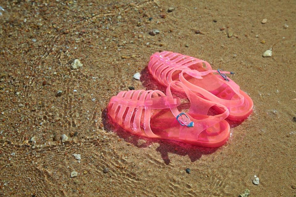 Pink Women's JELLY SANDALS on a sea shore. LADIES FLAT JELLIES SUMMER BEACH SHOES. Sand background - Image