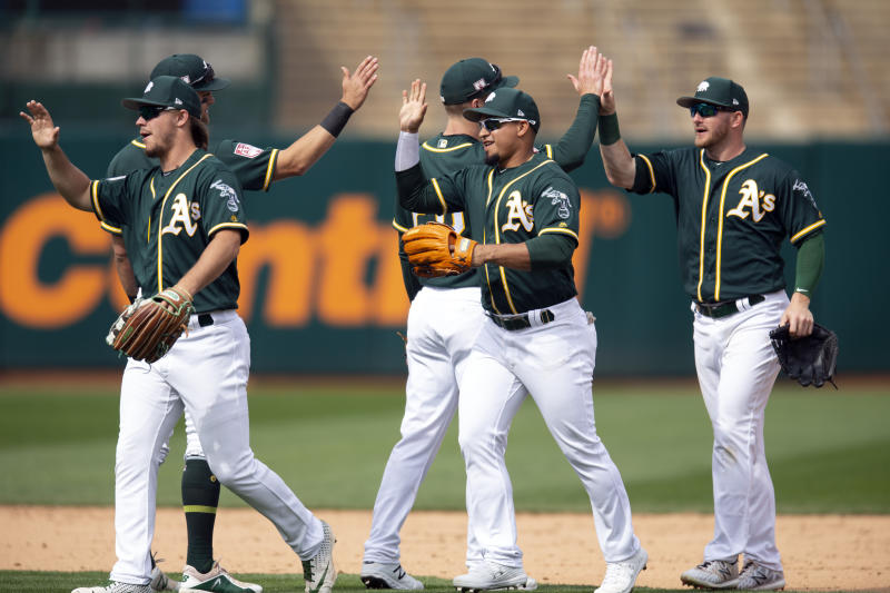 Oakland Athletics players celebrate their 5-0 victory over the San Francisco Giants in an exhibition baseball game, Sunday, March 24, 2019, in Oakland, Calif. (AP Photo/D. Ross Cameron)