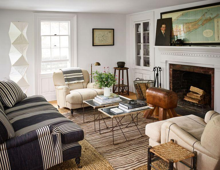 """<p>The neutral tones in the furniture, accessories, and framed maps add a rustic touch to this <a href=""""https://www.elledecor.com/design-decorate/house-interiors/a37082742/sherrill-farm-east-hampton-restoration/"""" rel=""""nofollow noopener"""" target=""""_blank"""" data-ylk=""""slk:historic Hamptons living room"""" class=""""link rapid-noclick-resp"""">historic Hamptons living room</a>—perfect for the fall season. </p>"""