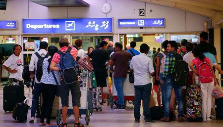 Tourists wait in the departures hall at Velana International Airport in Male