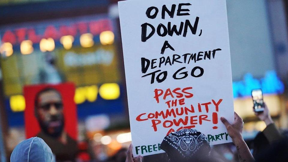 """A man holds up a sign saying """"one down, a department to go"""""""
