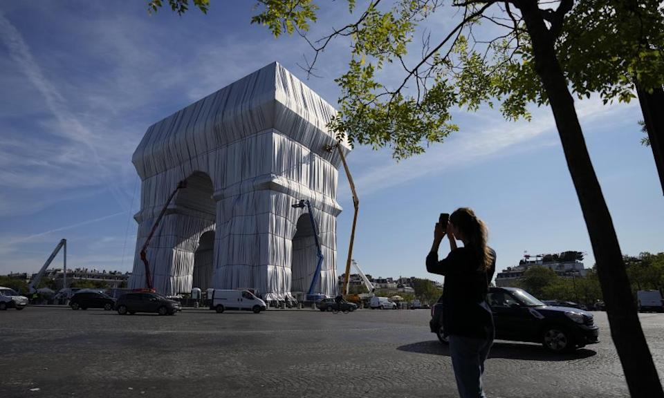 An onlooker takes a picture as workers put the final touches to the Arc's wrapping.