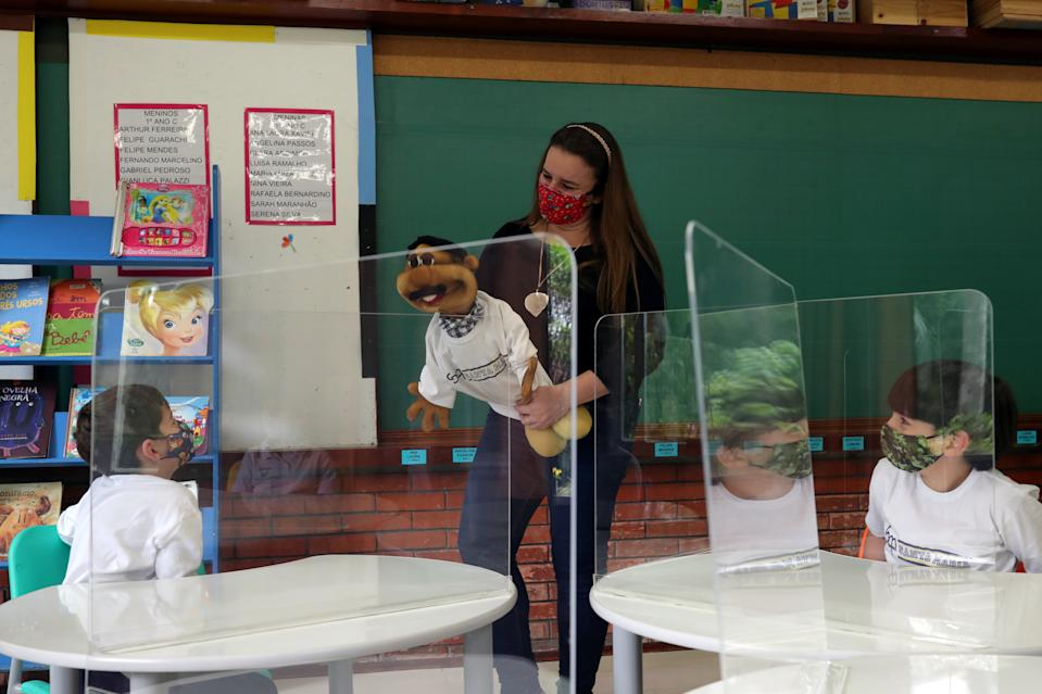 A teacher uses a doll during an activity with students at a classroom where plastic sheets are installed on desks for social distance and as a prevention measure at Santa Maria school amid the coronavirus disease (COVID-19) outbreak in Sao Paulo, Brazil November 3, 2020. REUTERS/Amanda Perobelli