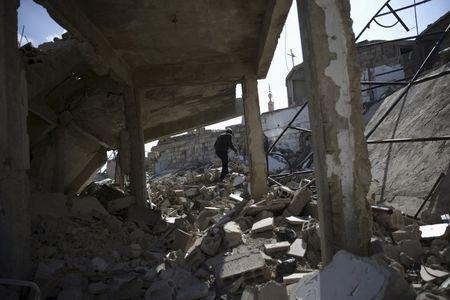 A man makes his way through rubble of damaged buildings in the Douma neighborhood of Damascus, Syria February 9, 2016. REUTERS/Bassam Khabieh