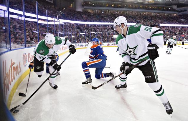 Dallas Stars' Tyler Seguin (91) and Jason Spezza (90) take control of the puck as Edmonton Oilers' Jeff Petry (2) defends during first period NHL hockey action in Edmonton, Alberta, on Sunday Dec. 21, 2014. (AP Photo/The Canadian Press, Jason Franson)