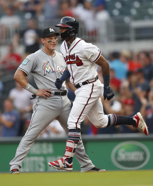 Atlanta Braves' Ronald Acuna Jr. (13) runs past Miami Marlins left fielder Derek Dietrich (32) as he rounds the bases after hitting a lead-off home run in the first inning of a baseball game Tuesday, Aug. 14, 2018 in Atlanta. (AP Photo/John Bazemore)