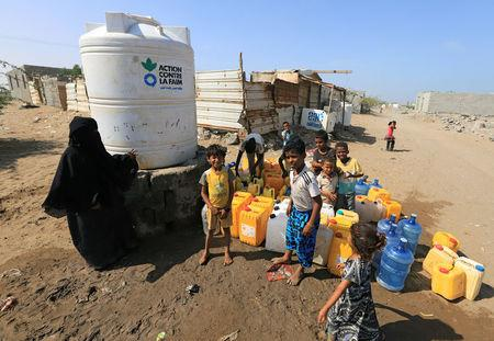 Children wait to fill jerry cans with drinking water on Salam Street in north Hodeidah