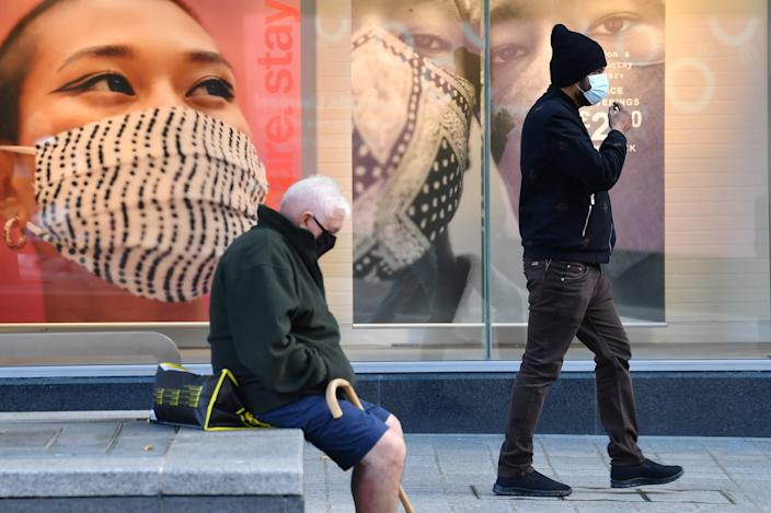 Pedestrian wearing facemasks walk past advertising for facemasks in central Liverpool, north west England on October 14, 2020, as new local lockdown measures come in to force to help stem a second wave of the novel coronavirus COVID-19. - The northwest city of Liverpool -- the only place put into the highest category -- will see a ban on household mixing and pub closures from today for at least four weeks. (Photo by Paul ELLIS / AFP) (Photo by PAUL ELLIS/AFP via Getty Images)