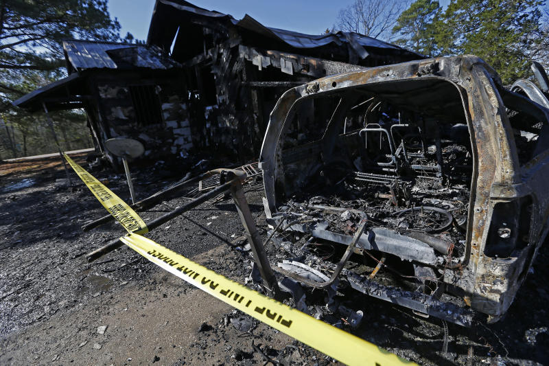 A vehicle and house is damaged from  a fatal fire on Saturday, Feb. 8, 2020 in Clinton, Miss. Authorities say a mother and her six children have been killed in the house fire in central Mississippi.  (AP Photo/Rogelio V. Solis)