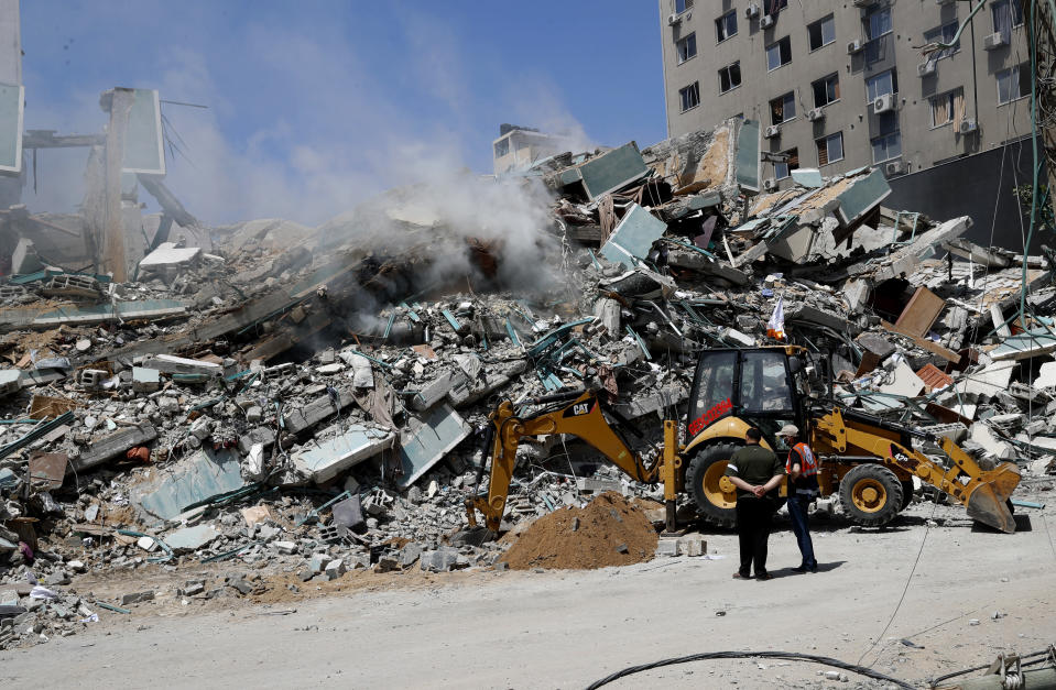 Workers clear rubble from a building that was destroyed by an Israeli airstrike on Saturday that housed The Associated Press, broadcaster Al-Jazeera and other media outlets, in Gaza City, Sunday, May 16, 2021. (AP Photo/Adel Hana)
