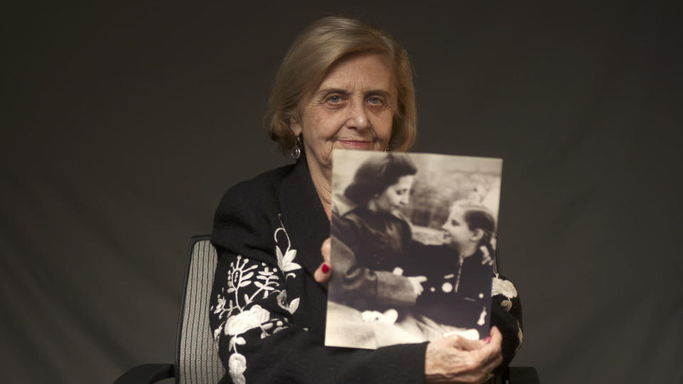 This photo provide by the World Jewish Congress, Tova Friedman, an 82-year-old Polish-born Holocaust survivor holding a photograph of herself as a child with her mother, who also survived the Nazi death camp Auschwitz, in New York, Friday, Dec.13, 2019. Friedman is delivering a warning against rising hatred in the world during an online commemoration on Wednesday, the 76th anniversary of the liberation of Auschwitz by Soviet troops at end of World War II. The commemorations for the victims of the Holocaust at the International Holocaust Remembrance Day, marking the liberation of Auschwitz-Birkenau on Jan. 27, 1945, will be mostly online in 2021 due to the coronavirus pandemic. (World Jewish Congress via AP)