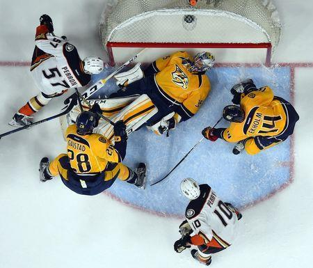 Apr 21, 2016; Nashville, TN, USA; Nashville Predators goalie Pekka Rinne (35) lays on the puck as Anaheim Ducks left winger David Perron (57) tries to score during the second period in game four of the first round of the 2016 Stanley Cup Playoffs at Bridgestone Arena. Christopher Hanewinckel-USA TODAY Sports