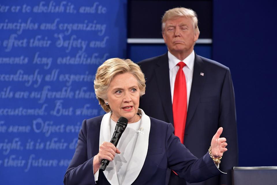Then-presidential candidate Donald Trump listens to his rival, Democrat Hillary Clinton, during the second presidential debate at Washington University in St. Louis on October 9, 2016.