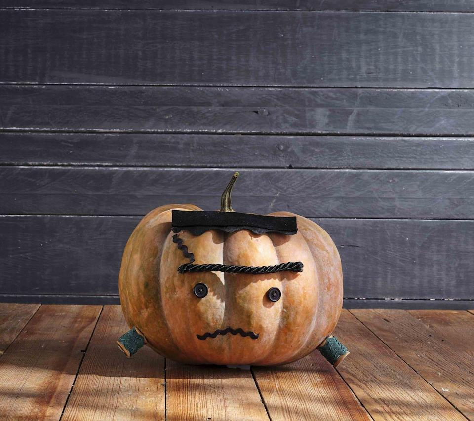 """<p>Is he friendly or is he not?! With rickrack spool bolts, how could he be anything other than sweet and cuddly.<strong><br></strong></p><p><strong>Make the pumpkin:</strong> Cut a length of extra-large black rickrack. Cut a piece of black felt the same length and attach it to the rickrack so that only the bottom """"ruffles"""" are showing. Attach the top of a flat-shaped heirloom pumpkin for hair. Attach two small black buttons to the center of the pumpkin with hot-glue for eyes. Attach a length of thick black cording above the eyes with hot-glue for eyebrow. Attach lengths of medium-size black rickrack to pumpkin with hot-glue for scar and mouth. Wrap two wooden spools with green rickrack and attach to the bottom sides of pumpkin with hot-glue for bolts.</p>"""