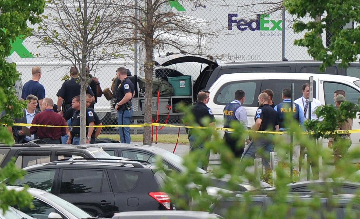"Police officials rope off the scene of a shooting at a FedEx facility in Kennesaw, Ga., on Tuesday, April 29, 2014. A shooter described as being armed with an assault rifle and having bullets strapped across his chest ""like Rambo"" opened fire Tuesday morning at a FedEx station outside Atlanta, wounding at least six people before police found the suspect dead from an apparent self-inflicted gunshot. (AP Photo/Atlanta Journal-Constitution, Brant Sanderlin) MARIETTA DAILY OUT; GWINNETT DAILY POST OUT; LOCAL TV OUT; WXIA-TV OUT; WGCL-TV OUT"