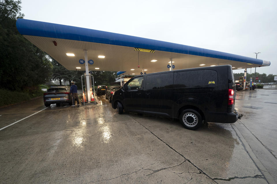 Vehicles fill up at a petrol station after an outbreak of panic buying in the UK, in Manchester, England, Monday, Sept. 27, 2021. British Prime Minister Boris Johnson is said to be considering whether to call in the army to deliver fuel to petrol stations as pumps ran dry after days of panic buying. ( AP Photo/Jon Super)