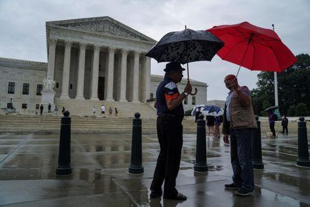 Men walk with umbrellas prior to the U.S. Supreme Court's decision to impose limits on the ability of police to obtain cellphone data pinpointing the past location of criminal suspects, outside the U.S. Supreme Court in Washington, U.S., June 22, 2018. REUTERS/Toya Sarno Jordan