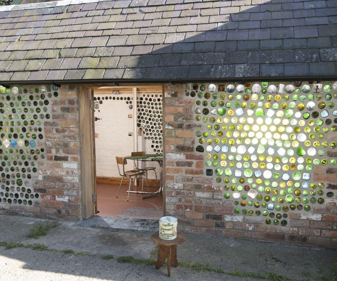 <p><strong>ECO FINALIST</strong> – owned by Lauretta and Philip Denton.</p><p>Inspired by a story written by her primary school teacher, Mrs. Arnold, Lauretta set out to build her bottle shed with the help of her detail-oriented husband Philip. The space, built entirely of repurposed staircases, windows, doors and bottles was a fluid process, which started without a plan. Each repurposed piece fitted perfectly as though it was always meant to be part of this extraordinary shed. Today, Bottle Shed holds memories and stories, from a collage of buttons Lauretta collected from her mum and grandmother, to messages and ships in bottles.</p>