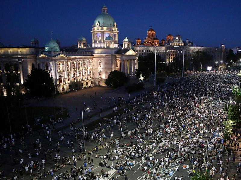 Demonstrators peacefully sit on the street in front of the parliament during a protest in Belgrade: Olive Bunic/AFP via Getty Images
