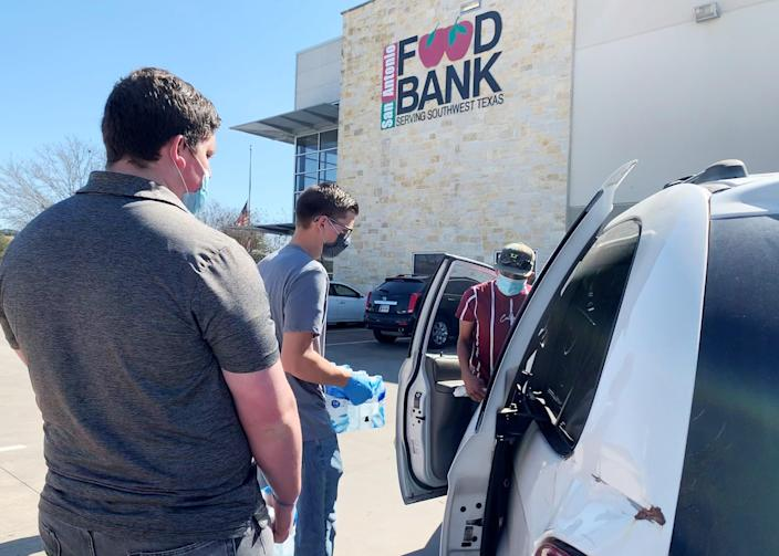 Michael Ybarra, right, had tried to get groceries during the storm but his car broke down. He was picking up water being distributed by the San Antonio food bank. (Suzanne Gamboa / NBC News)