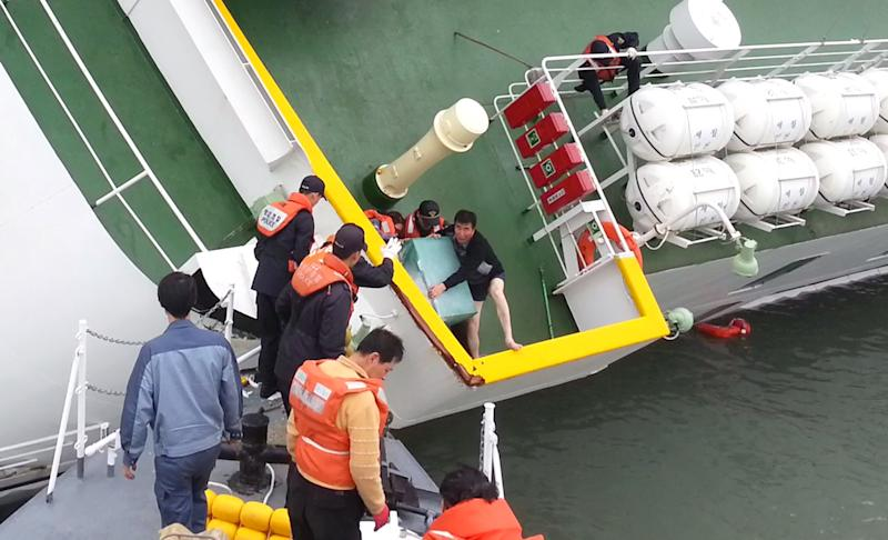 """A video screen grab released by Korea Coast Guard on April 28, 2014 shows """"Sewol"""" captain Lee Joon-Seok (centre R) being rescued from the tilting vessel before it sank on April 16, 2014 (AFP Photo/Korea Coast Guard)"""