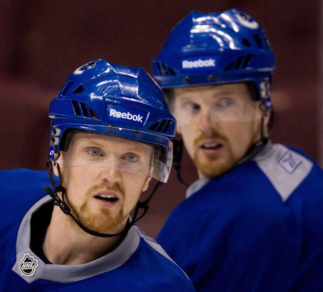 FILE - In this April 12, 2011, file photo, Henrik Sedin, left, and his twin brother Daniel Sedin look on during NHL hockey practice in Vancouver, British Coumbia. The twin superstarssigned four-year contract extensions with the Canucks. the team announced Friday, Nov. 1, 2013. (AP Photo/The Canadian Press, Darryl Dyck, File)