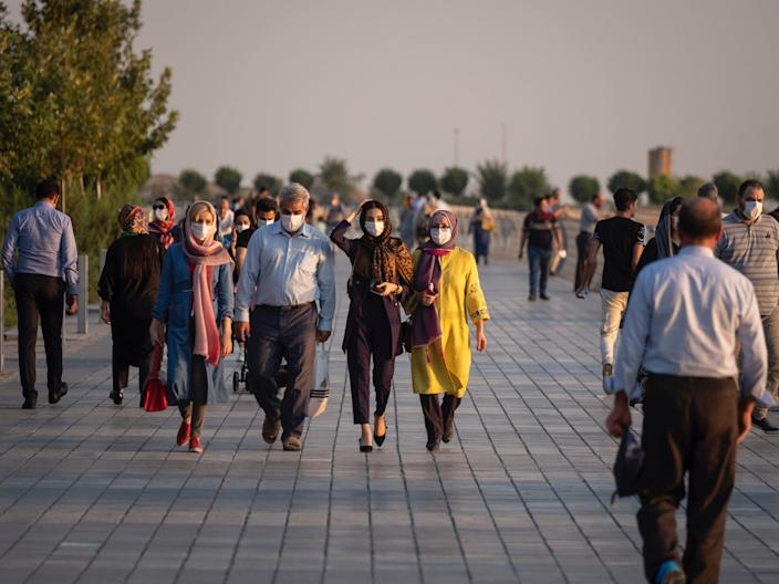 """An Iranian family wearing protective face masks walk along an area in the recreational Chitgar complex in northwestern Tehran at sunset on August 13, 2020. <p class=""""copyright"""">Morteza Nikoubazl/NurPhoto via Getty Images</p>"""