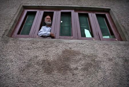 Kashmiri man looks out from a window of his house which was allegedly damaged by Indian security forces after clashes between protesters and the security forces on Friday evening, in Srinagar