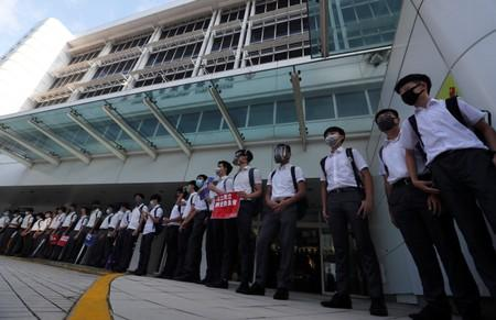 Secondary school students form a human chain as they demonstrate against what they say is police brutality against protesters, after clashes at Wan Chai district, in Hong Kong
