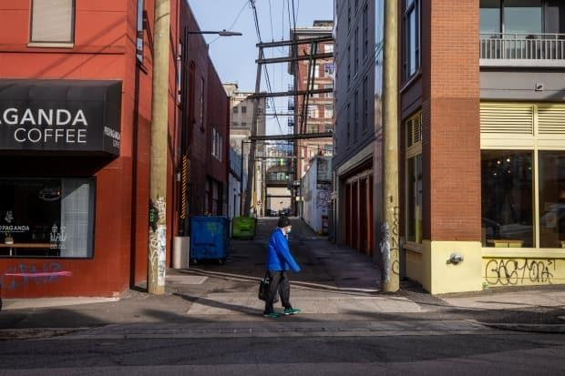 A person wearing a face mask walks by an alleyway in Chinatown in Vancouver on Feb. 24, 2021.