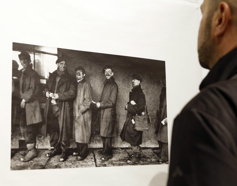 """FILE - In this Jan. 28, 2016 file photo, a man looks at a photograph by Robert Frank at the opening of the exhibition featuring Frank's work, """"Robert Frank: Books and Films, 1947–2016,"""" at New York University's Tisch School of the Arts in New York. Frank, one of the 20th century's greatest photographers, has died at age 94. Frank died Monday, Sept. 9, 2019, in Inverness, on Cape Breton Island in Nova Scotia, where he had a summer home, The New York Times reports.  (AP Photo/Kathy Willens, File)"""