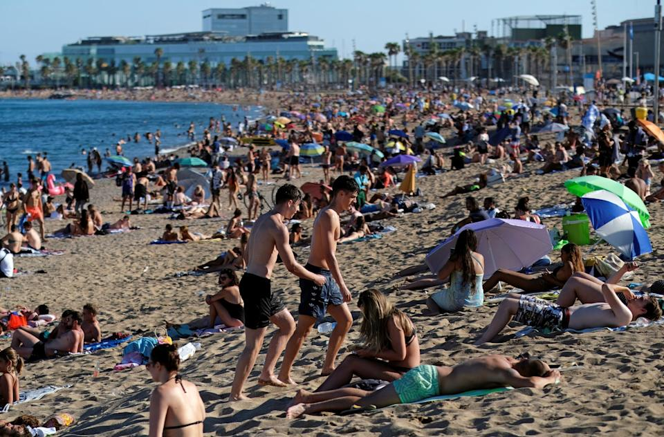 People enjoy the sunny weather at Barceloneta beach, after Catalonia's regional authorities and the city council announced restrictions to contain the spread of the coronavirus disease: REUTERS