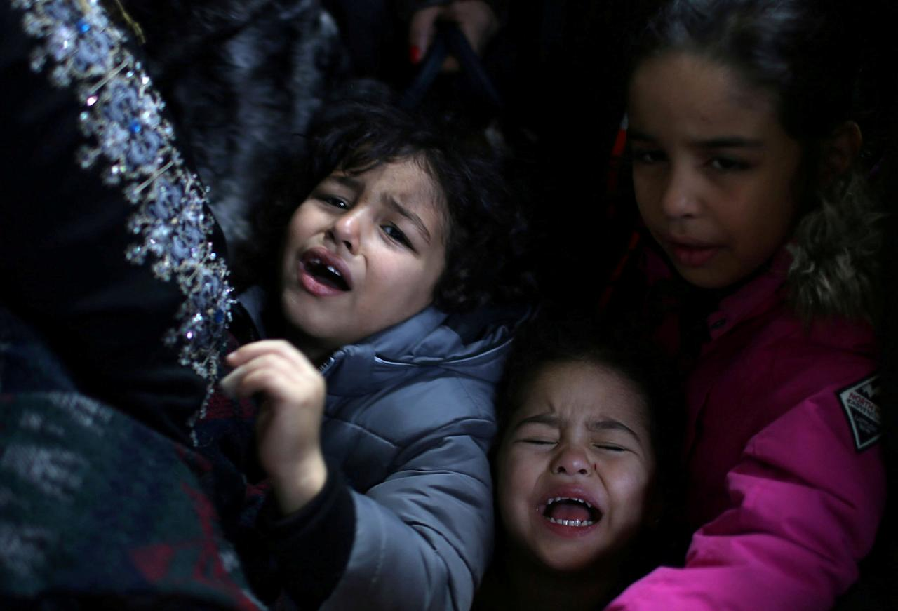 Children cry as they wait with their family for travel permits to cross into Egypt through the Rafah border crossing after it was opened by Egyptian authorities for humanitarian cases, in the southern Gaza Strip December 18, 2017. REUTERS/Ibraheem Abu Mustafa     TPX IMAGES OF THE DAY