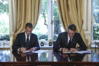 Greece's Prime Minister Kyriakos Mitsotakis, right and UEFA President Aleskander Ceferin, sign an agreement, during their meeting in Athens, Tuesday, Feb. 25, 2020. Mitsotakis requested UEFA's help to clean up Greek soccer last month and has said he was willing to request expulsion of Greece's teams from European competition and even suspend the league unless major clubs sign up to a reform plan aimed stamping out match-related violence and widespread allegations of corruption in the sport. (AP Photo/Petros Giannakouris)
