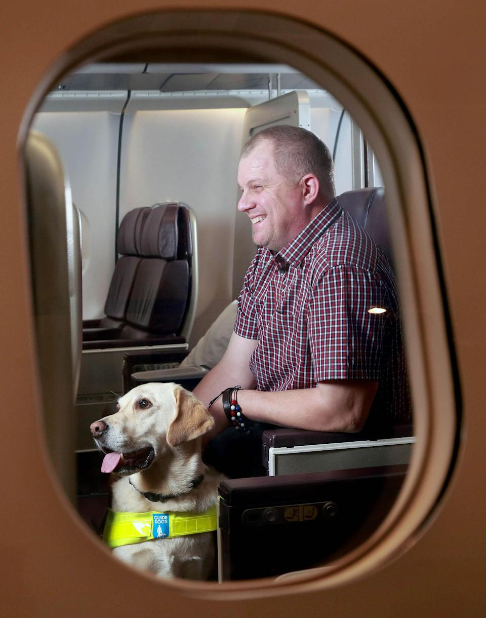 <p>Paul Smith, Guide Dogs for the Blind and guide dog Pedro try out a new range of in-flight technology (IFE), developed specifically for visually impaired customers on board Virgin Atlantic services, at Gatwick in West Sussex. (PA) </p>