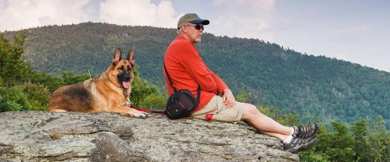 Senior man sitting on rock with German Shepherd dog in a field off the Appalachian Trail on Roan Mountain border of North Carolina and Tennessee.
