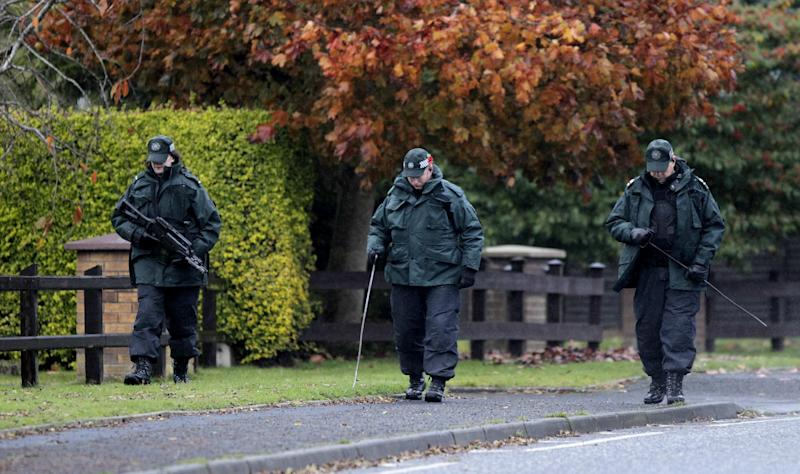 Police Service of Northern Ireland officers search the area close to a fatal shooting on the M1 motorway near Lurgan, Northern Ireland, Thursday, Nov. 1, 2012. A veteran Northern Ireland prison officer was killed Thursday in a gun ambush as he was driving to work, the first slaying of a security-force member in the British territory in 18 months. Police said a gunman in a passing car shot David Black, 52, as he drove onto the M1 motorway southwest of Belfast. His car plummeted down a grassy embankment into a ditch.   (AP Photo/Peter Morrison)