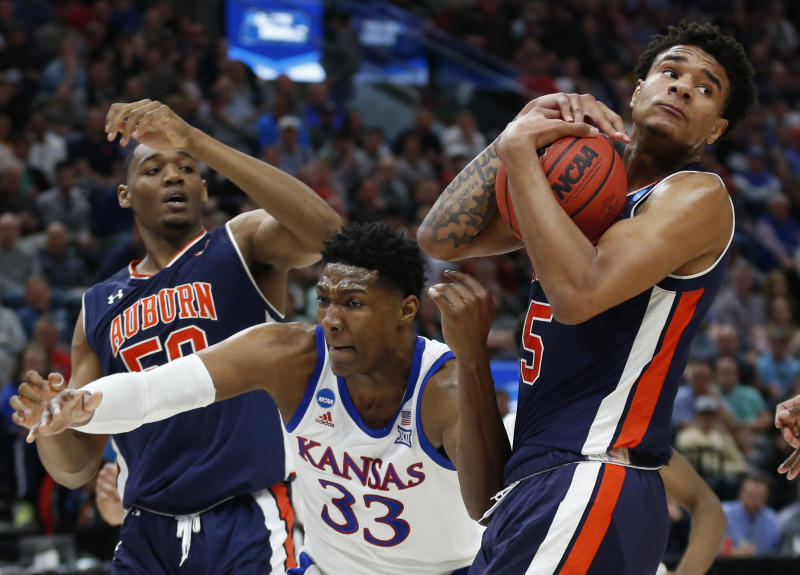 Auburn's Chuma Okeke (5) grabs a rebound from Kansas forward David McCormack (33) as Auburn's Austin Wiley (50) watches during the first half of a second-round game in the NCAA men's college basketball tournament Saturday, March 23, 2019, in Salt Lake City. (AP Photo/Rick Bowmer)