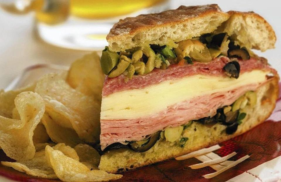 """<p>A New Orleans-inspired muffuletta is the <a href=""""https://www.thedailymeal.com/recipe/game-day-recipes-football?referrer=yahoo&category=beauty_food&include_utm=1&utm_medium=referral&utm_source=yahoo&utm_campaign=feed"""" rel=""""nofollow noopener"""" target=""""_blank"""" data-ylk=""""slk:ultimate game day sandwich"""" class=""""link rapid-noclick-resp"""">ultimate game day sandwich</a>. Italian bread is spread with a homemade olive salad and piled high with mortadella, salami and provolone cheese. The olive salad needs to chill in the fridge for three hours before serving, so it's best to prep this sandwich the night before.</p> <p><a href=""""https://www.thedailymeal.com/recipes/tailgate-muffuletta-sandwich-recipe?referrer=yahoo&category=beauty_food&include_utm=1&utm_medium=referral&utm_source=yahoo&utm_campaign=feed"""" rel=""""nofollow noopener"""" target=""""_blank"""" data-ylk=""""slk:For the Tailgate Muffuletta Sandwich recipe, click here."""" class=""""link rapid-noclick-resp"""">For the Tailgate Muffuletta Sandwich recipe, click here.</a></p>"""
