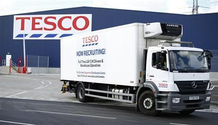 A lorry with job advertisements on its side leaves a Tesco distribution centre in Dagenham, east London