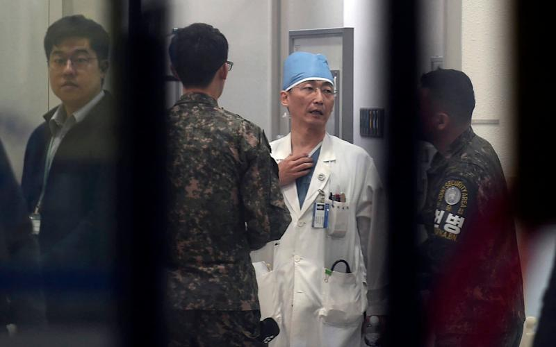 South Korean soldiers talk with a medic preparing to treat an unidentified injured person, unseen, believed to be a North Korean soldier, at a hospital in Suwon - Newsis