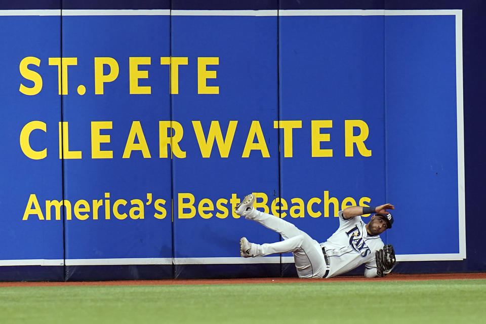 Tampa Bay Rays center fielder Kevin Kiermaier falls to the track after making a catch in the third inning of a fly ball hit by Boston Red Sox's Rafael Devers in Game 2 of a baseball American League Division Series, Friday, Oct. 8, 2021, in St. Petersburg, Fla. (AP Photo/Chris O'Meara)