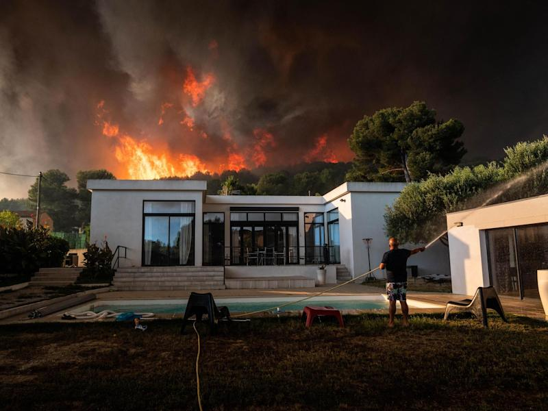 A man uses a garden hose to drench his house before being evacuated as a wild fire burns in the background, in La Couronne, near Marseille: AFP/Getty