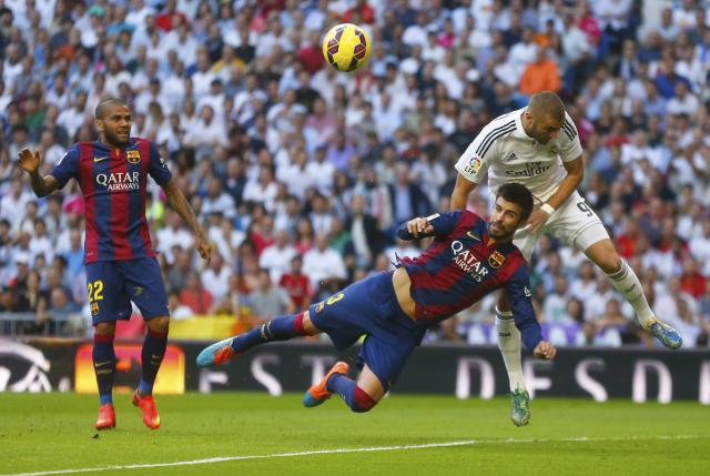 "Barcelona's Gerard Pique (C) fights for the ball against Real Madrid's Karim Benzema (R) as Barcelona's Daniel Alves looks on during their Spanish first division ""Clasico"" soccer match at the Santiago Bernabeu stadium in Madrid October 25, 2014. REUTERS/Juan Medina (SPAIN - Tags: SOCCER SPORT)"