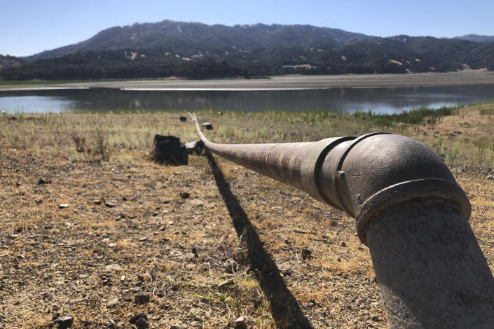 """A pipe runs to Lake Mendocino near Ukiah, Calif., on Wednesday, Aug. 4, 2021. Tourists flock to the picturesque coastal town of Mendocino for its Victorian homes and cliff trails, but visitors this summer will also find public portable toilets and dozens of signs on picket fences announcing the quaint Northern California hamlet: """"Severe Drought Please conserve water."""" The town of Mendocino gets some of their water from the reservoir, but most of the lake water goes to Sonoma County. (AP Photo/Haven Daley)"""