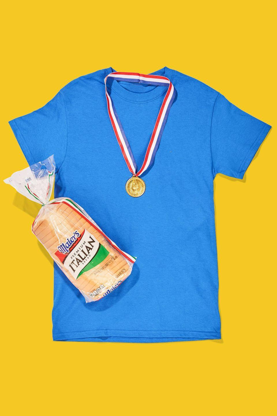 """<p>Throw on a brightly colored t-shirt and a fake medal, grab a loaf, and you're ready to get that bread. </p><p><a class=""""link rapid-noclick-resp"""" href=""""https://www.amazon.com/Costume-Accessory-Olympic-Style-Plastic/dp/B005EJCHV2/?tag=syn-yahoo-20&ascsubtag=%5Bartid%7C10070.g.490%5Bsrc%7Cyahoo-us"""" rel=""""nofollow noopener"""" target=""""_blank"""" data-ylk=""""slk:SHOP FAKE MEDALS"""">SHOP FAKE MEDALS</a> </p>"""